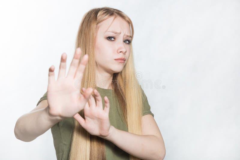Mulher triste nova que aumenta as palmas no nenhum ou no gesto da parada, querendo diminuir a oferta foto de stock