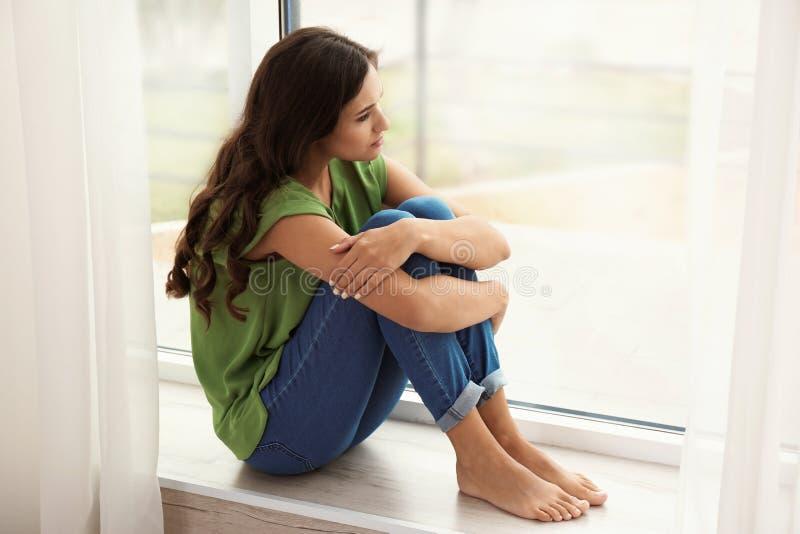 Mulher triste nova que senta-se perto da janela imagens de stock