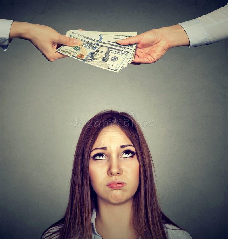 Mulher triste preocupada que olha acima em duas mãos que trocam o dinheiro imagens de stock royalty free