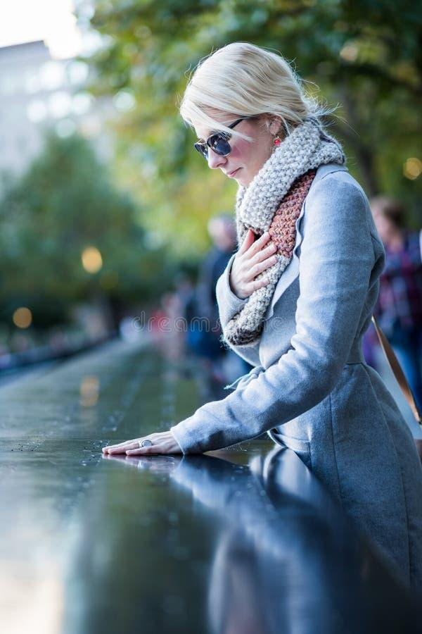 Mulher triste que olha os nomes do memorial do World Trade Center imagem de stock