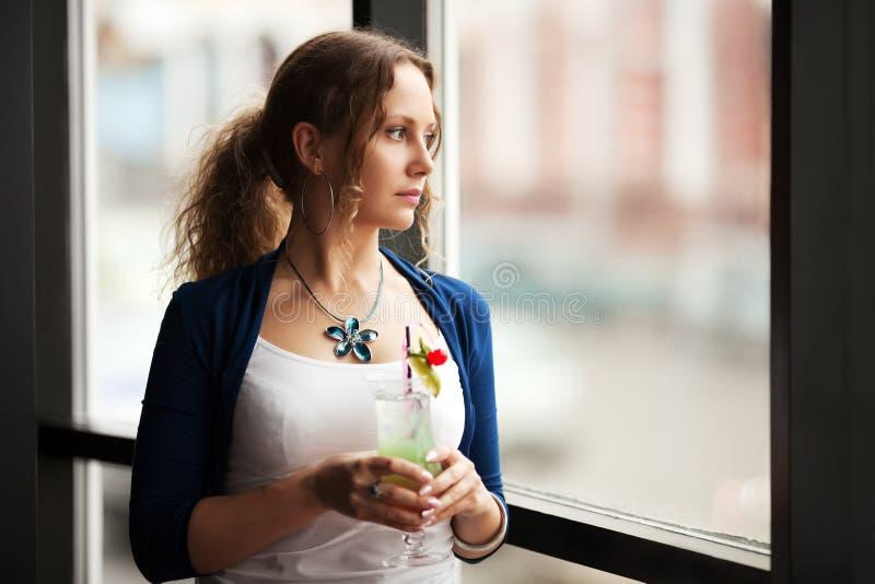Mulher triste que olha para fora a janela imagens de stock royalty free