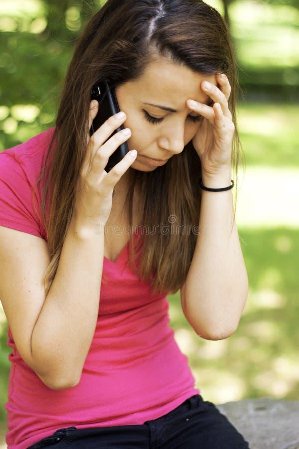Mulher triste que recebe a notícia ruim pelo telefone fotografia de stock