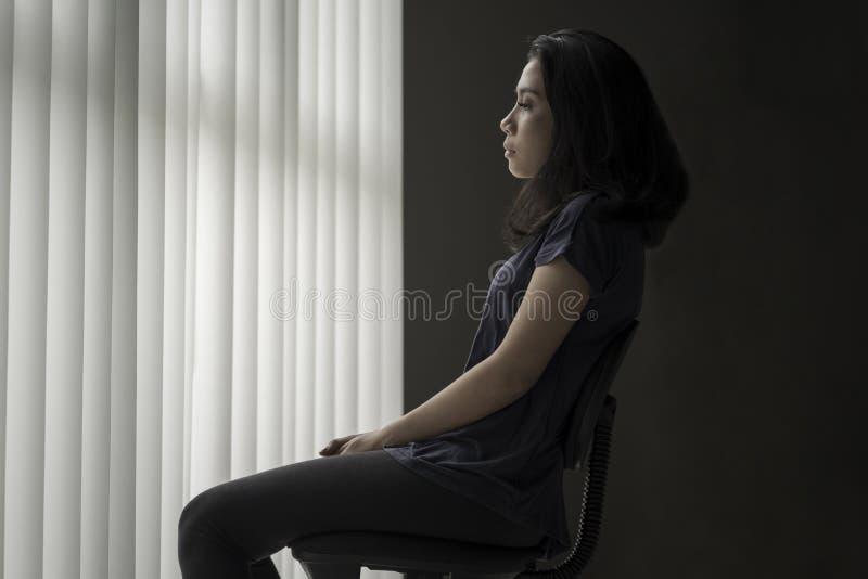 Mulher triste que senta-se na cadeira fotografia de stock