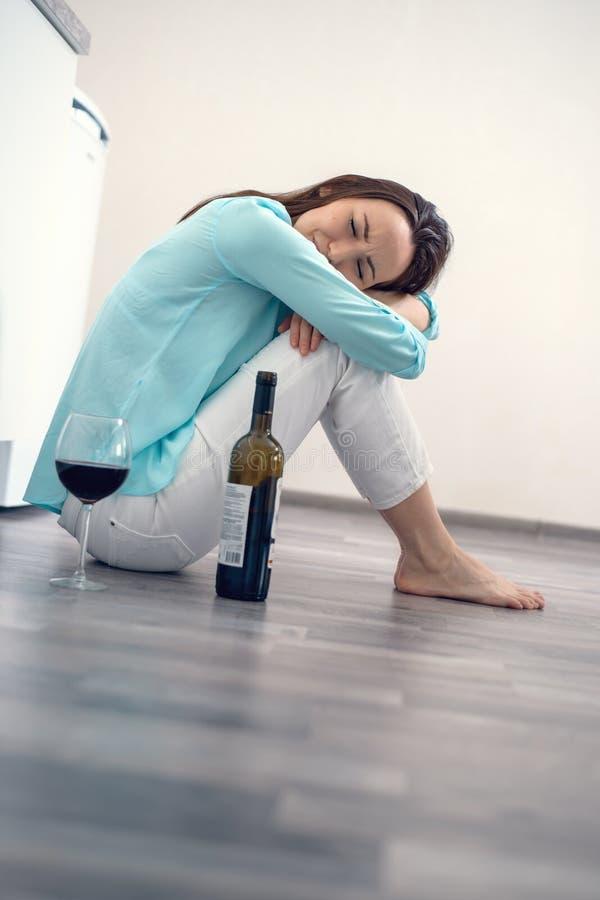 Mulher triste que senta-se no assoalho que abraça seus joelhos com uma garrafa do vinho tinto que grita, conceito do divórcio, di imagem de stock royalty free
