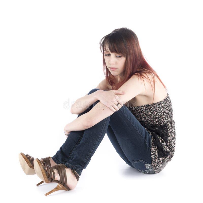 Mulher triste que senta-se no assoalho que abraça seu joelho imagens de stock