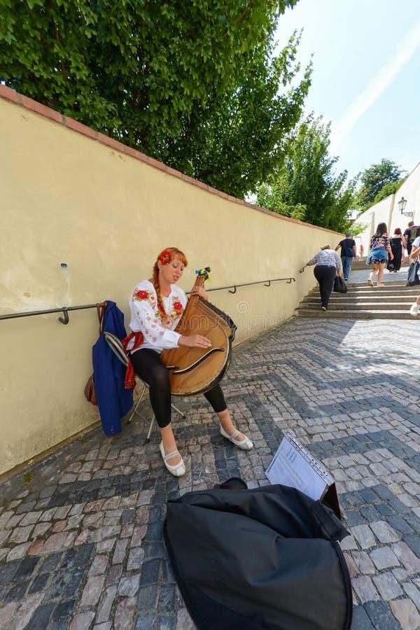 Mulher ucraniana bonita que joga um bandura do instrumento musical nas ruas de Praga imagens de stock