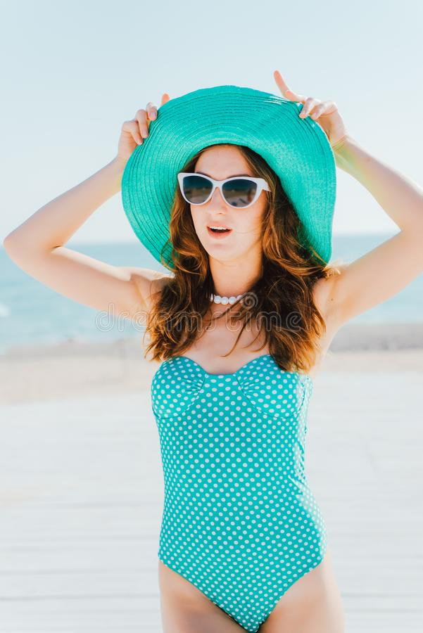 A mulher um chapéu e um roupa de banho nas ervilhas está contra imagem de stock royalty free