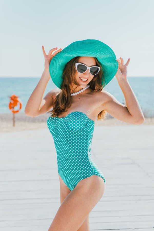 A mulher um chapéu e um roupa de banho nas ervilhas está contra fotos de stock royalty free