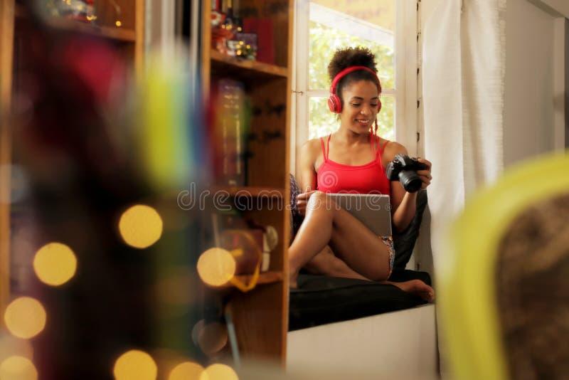 A mulher usa a conexão sem fio entre a câmera da foto e o portátil imagens de stock