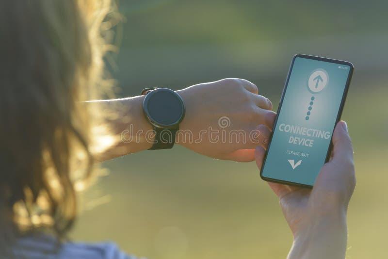 A mulher usa o smartwatch e o telefone esperto fotografia de stock royalty free