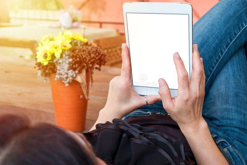 A mulher usa a tabuleta ao relaxar em casa com café em f de madeira foto de stock royalty free
