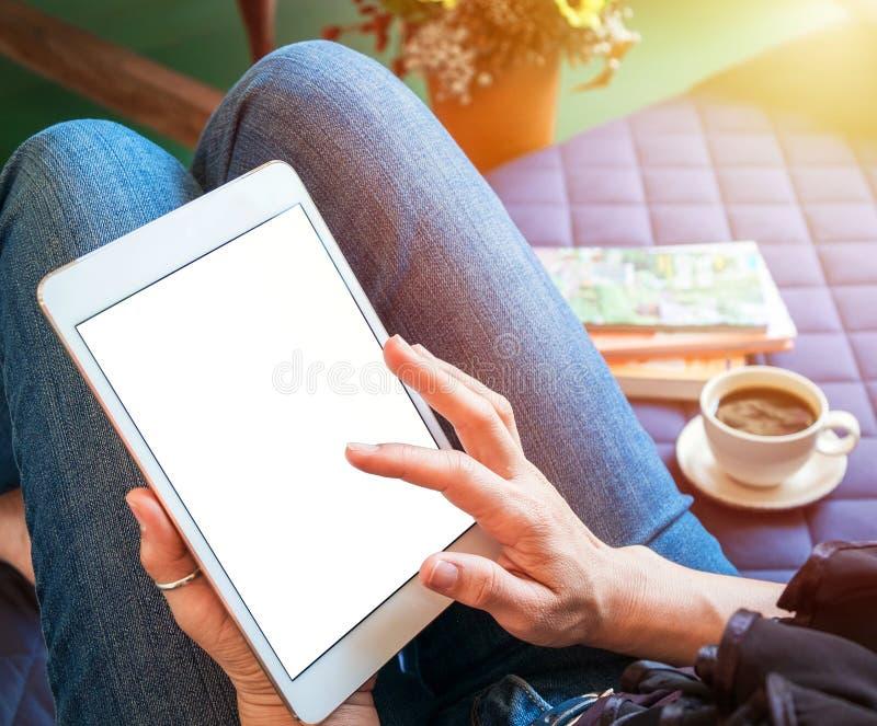 A mulher usa a tabuleta ao relaxar em casa com café no sofá fotografia de stock royalty free