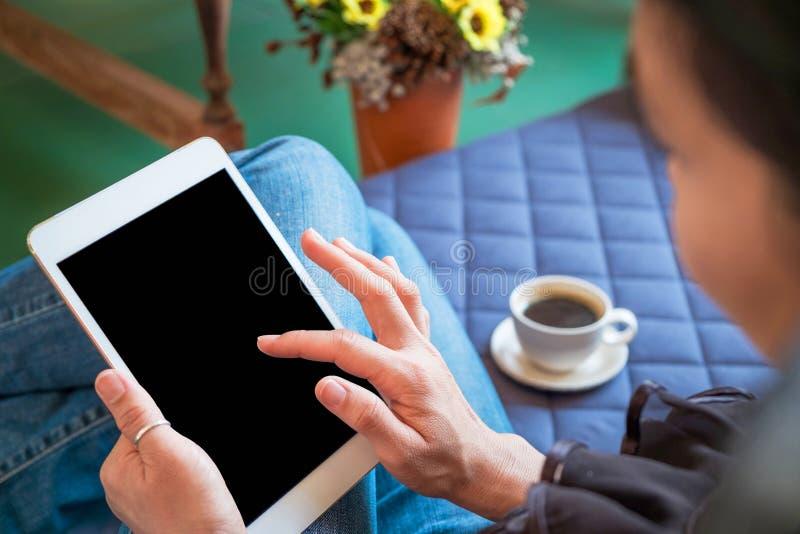A mulher usa a tabuleta ao relaxar em casa com café no sofá imagens de stock royalty free
