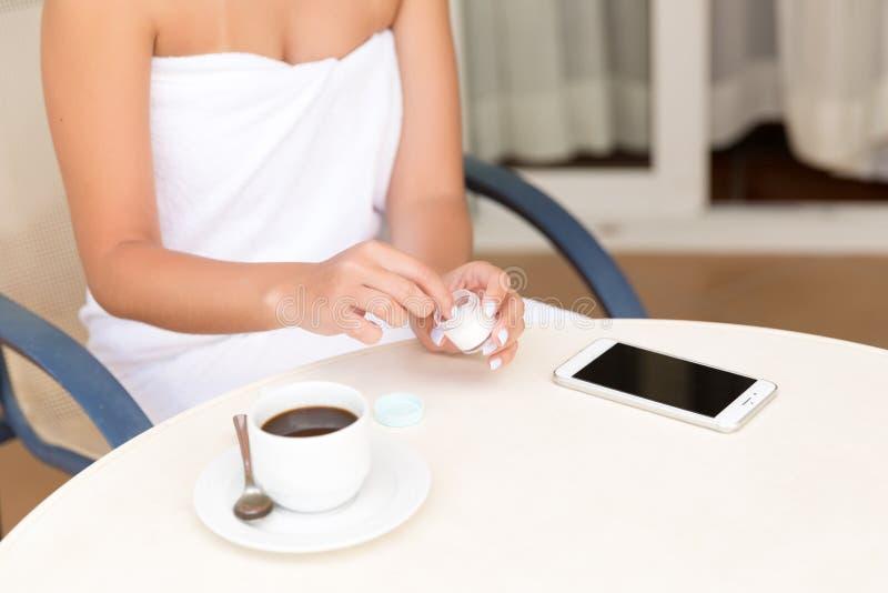 A mulher usa um frasco do creme para o produto dos cuidados com a pele Creme hidratante nas mãos fêmeas Skincare da beleza e conc imagens de stock