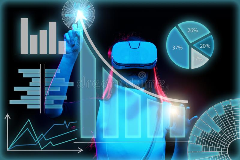 A mulher usa uns auriculares da realidade virtual para trabalhar com dados sob a forma dos gráficos e das cartas fotos de stock