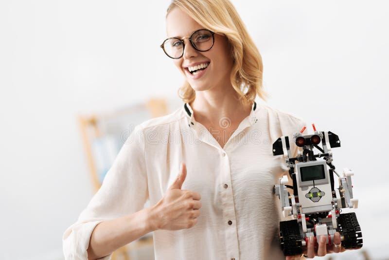 Mulher vívida que demonstra o robô pequeno digital dentro foto de stock royalty free