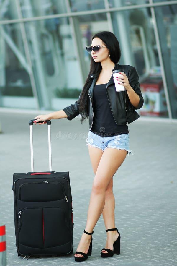 A mulher vai curso com bagagem no aeroporto internacional de Lviv e no d imagem de stock