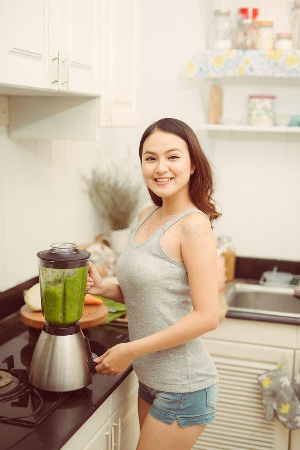 Mulher vegetal do batido que mistura batidos verdes com a casa do misturador na cozinha imagens de stock
