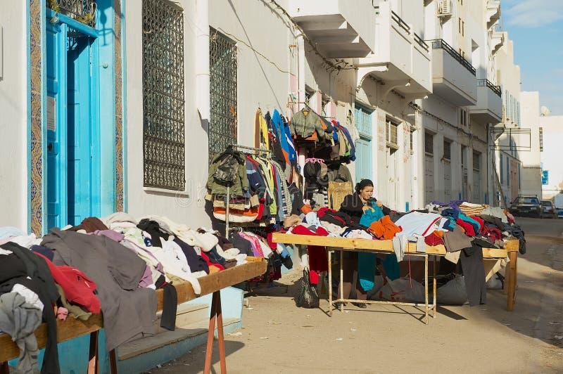 A mulher vende bens de mão dos secons na rua no medina de Sfax, Tunísia fotografia de stock