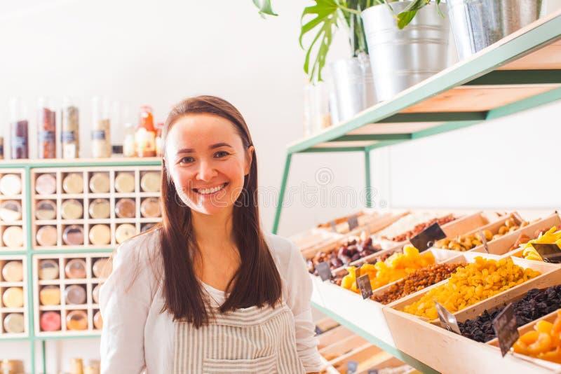 A mulher vende frutos e especiarias secos nas compras na mercearia imagens de stock