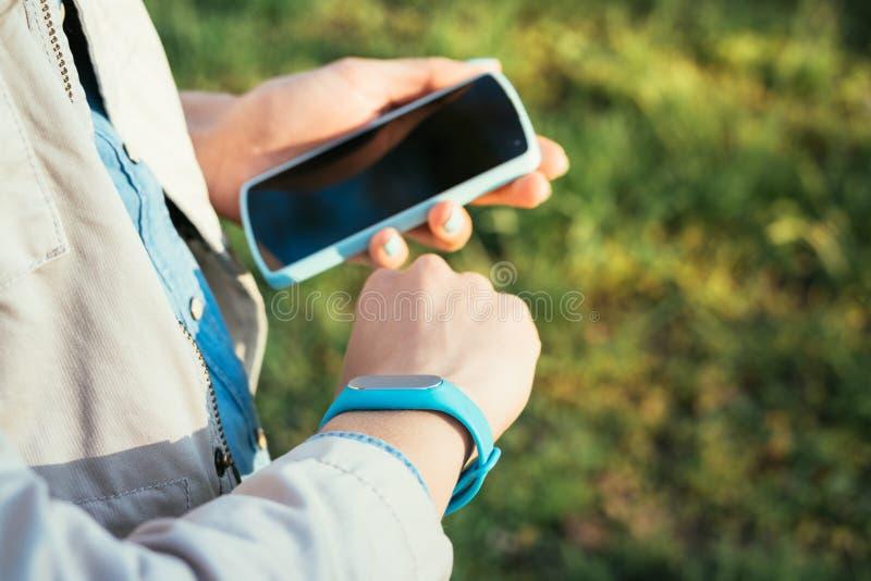 A mulher verifica dados do bracelete da aptidão em um telefone celular imagem de stock royalty free