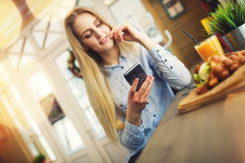 A mulher verifica a notícia nas redes sociais em seu telefone em um café acolhedor ao estilo de Provence imagens de stock