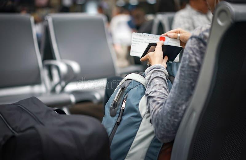 A mulher verifica seus passaporte e bilhete plano na mão e em esperar o plano em um aeroporto internacional, Tailândia imagens de stock royalty free