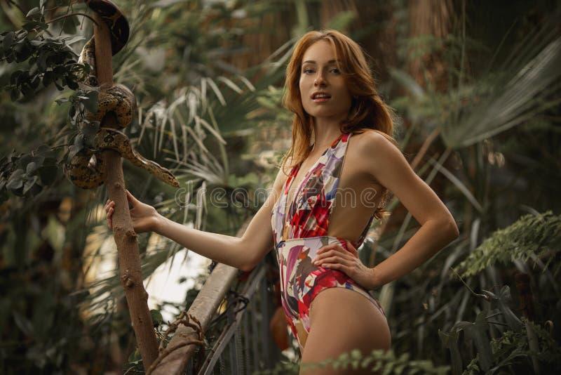 Mulher vermelha atrativa com pitão Menina bonita do gengibre para observar para a serpente no jardim tropical Mulher caucasiano a fotos de stock royalty free