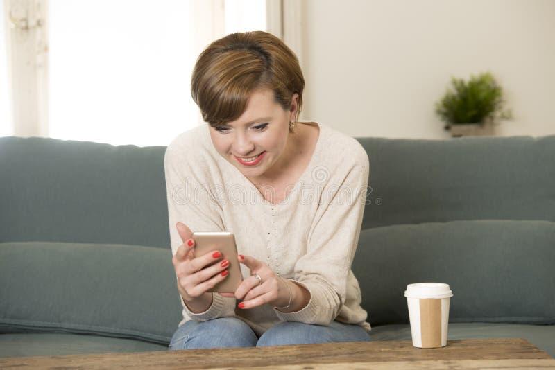 Mulher vermelha atrativa e feliz nova do cabelo que senta em casa o sofá c fotografia de stock