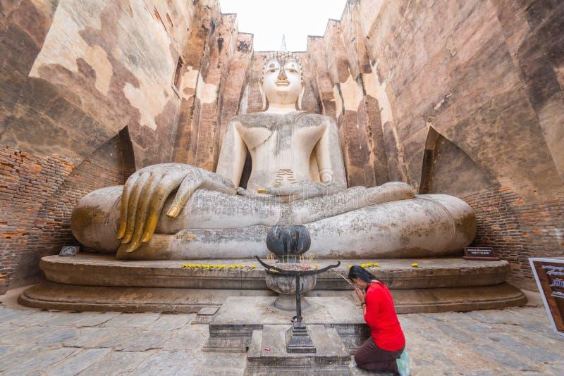 Mulher vermelha da camisa que paga o respeito à imagem a maior da Buda imagens de stock