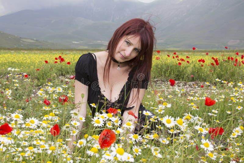 Mulher vermelha do cabelo em flores imagem de stock royalty free