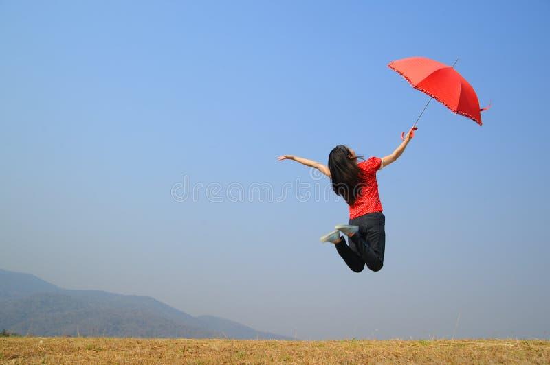 A mulher vermelha do guarda-chuva salta ao céu azul imagem de stock royalty free