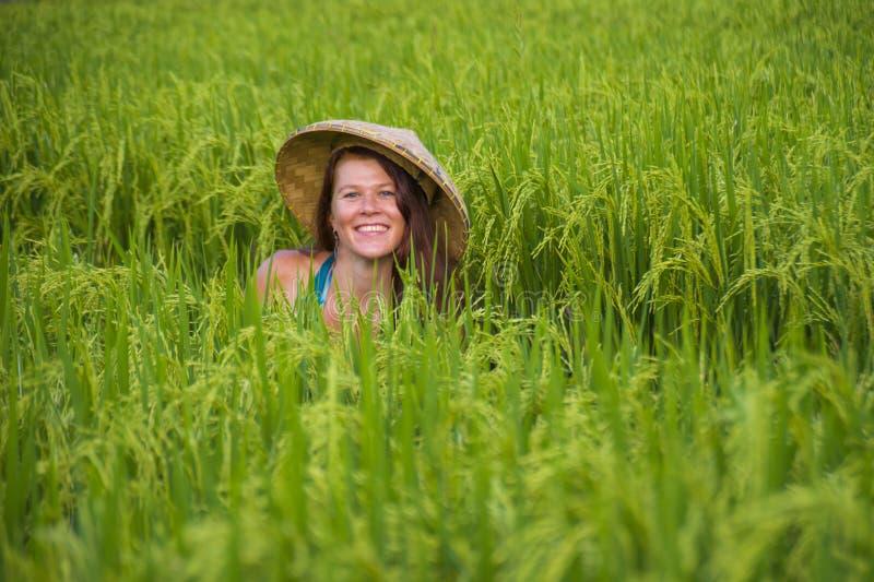 Mulher vermelha feliz e bonita nova do cabelo em alegre de sorriso do chap?u asi?tico tradicional do fazendeiro isolada no campo  foto de stock