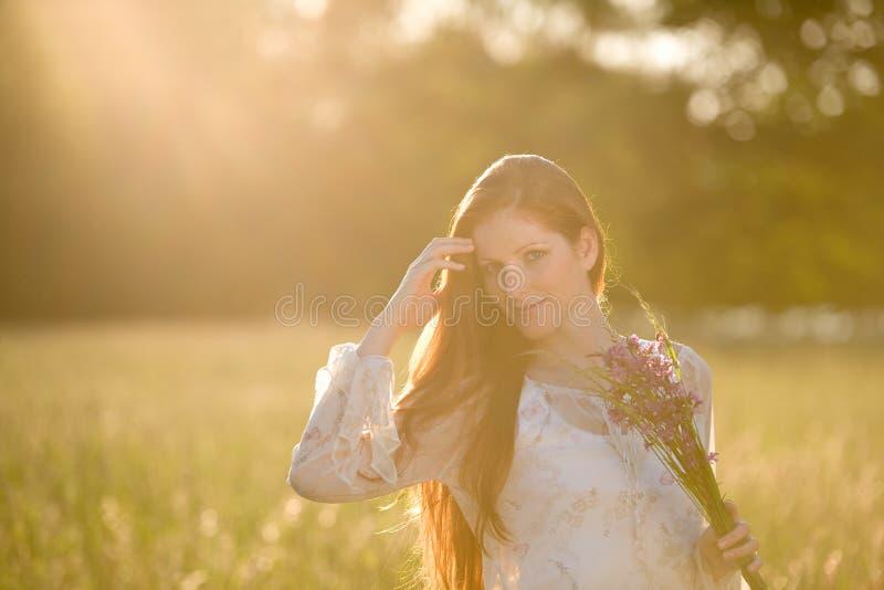 Mulher vermelha longa do cabelo no prado romântico do por do sol imagens de stock royalty free
