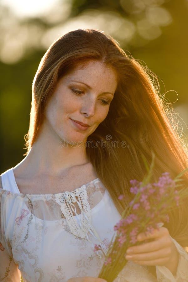 Mulher vermelha longa do cabelo no prado romântico do por do sol imagem de stock