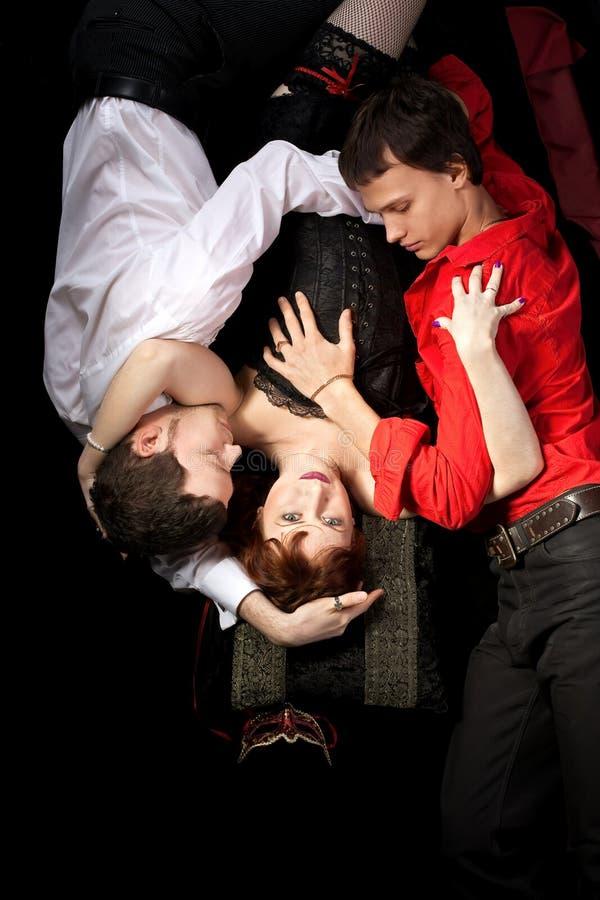 Mulher vermelha na máscara e dois homens - triângulo de amor foto de stock royalty free