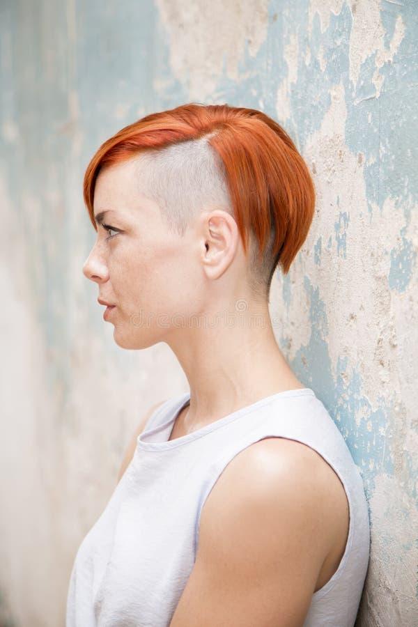 Mulher vermelha nova do cabelo pela parede velha imagem de stock royalty free