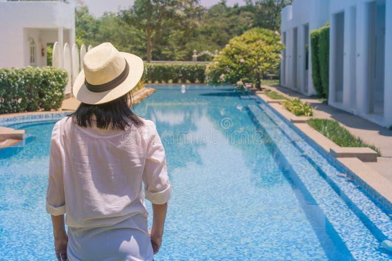 A mulher veste a camisa branca e tece o chapéu, que ela a posição relaxa na borda da piscina foto de stock