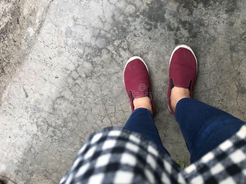 A mulher veste a camisa de manta, as calças de brim e as sapatas vermelhas estando na rua concreta imagens de stock