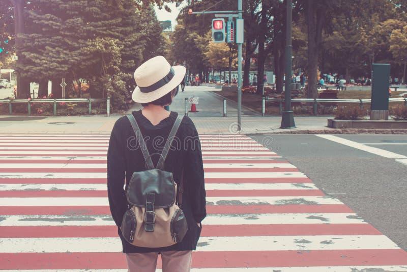 A mulher veste o branco tece o chapéu e o sobretudo preto Ela que está no passeio e que espera cruzando a estrada fotografia de stock royalty free
