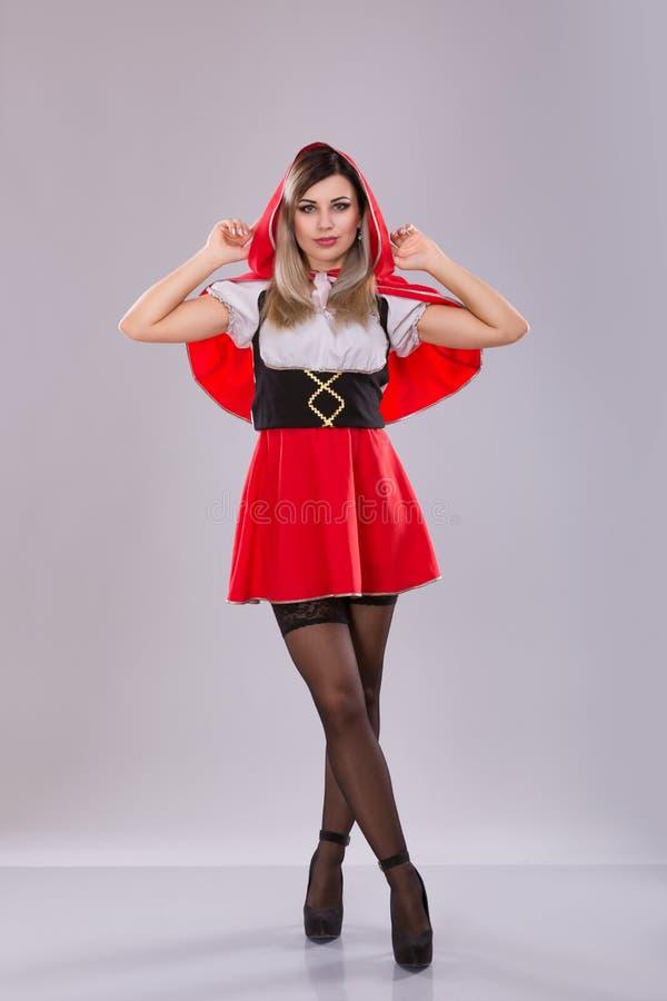 Mulher vestida como pouca capa de equitação vermelha imagem de stock