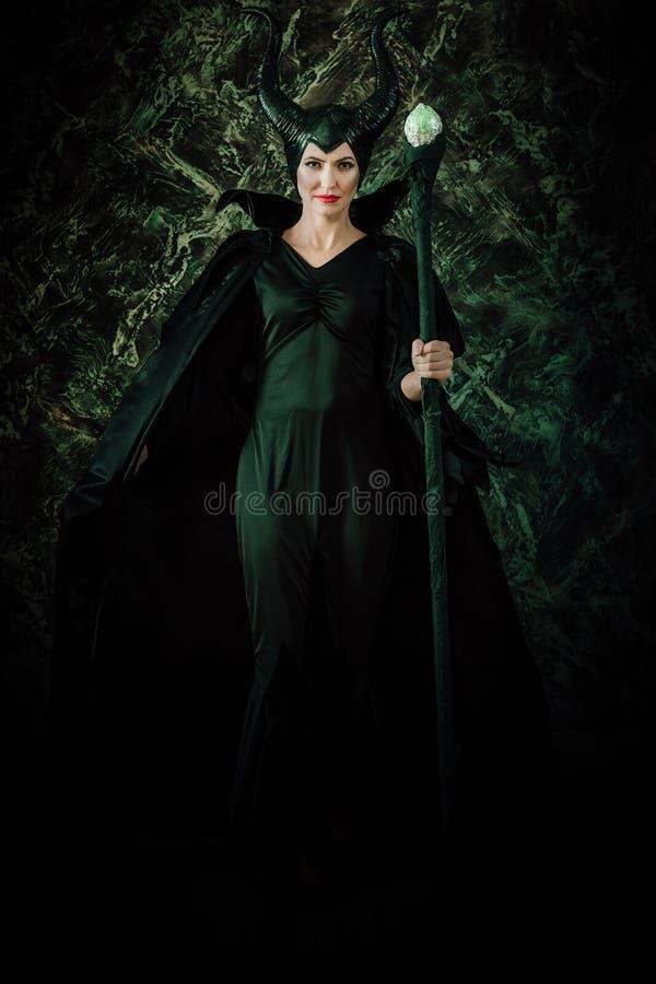 Mulher vestida como uma bruxa feericamente na capa de chuva e com chifres imagens de stock royalty free