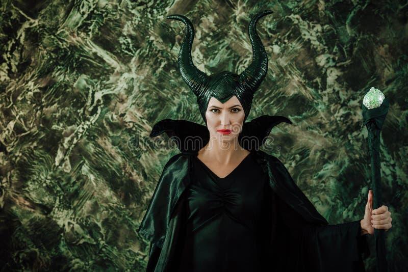 Mulher vestida como uma bruxa feericamente na capa de chuva e com chifres foto de stock royalty free