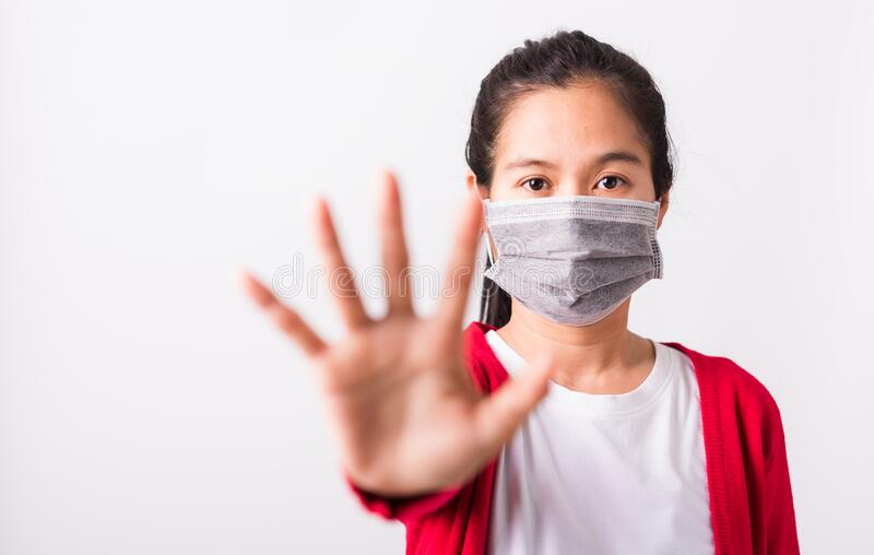 Mulher vestindo máscara protetora contra coronavírus ou poeira filtrante, poluição do ar que levanta a mão da palma para não usar fotos de stock royalty free