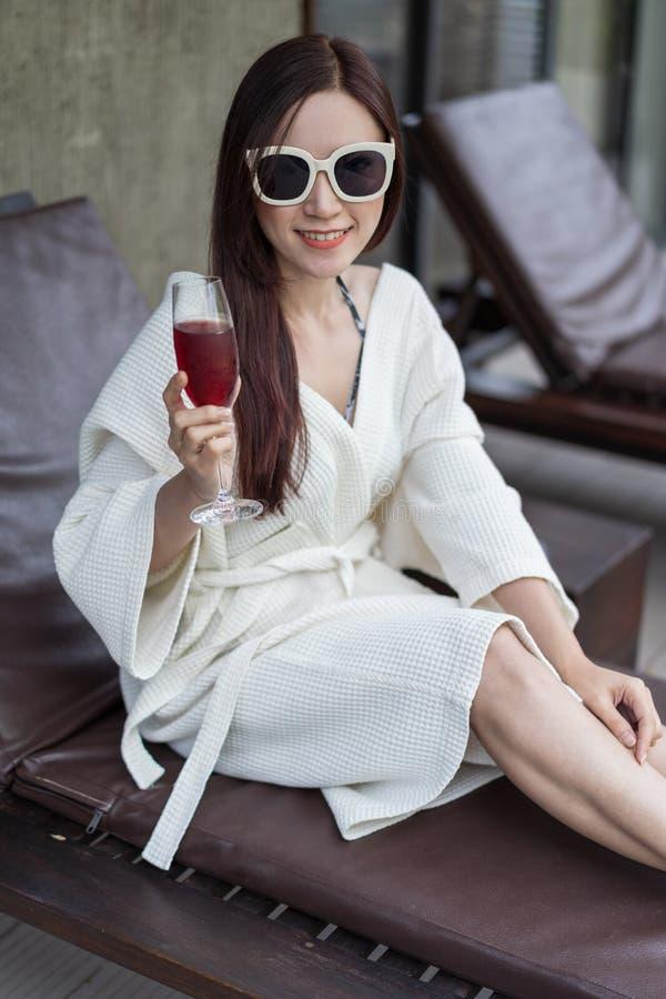 A mulher vestiu o roupão que senta-se no deckchair na associação foto de stock royalty free