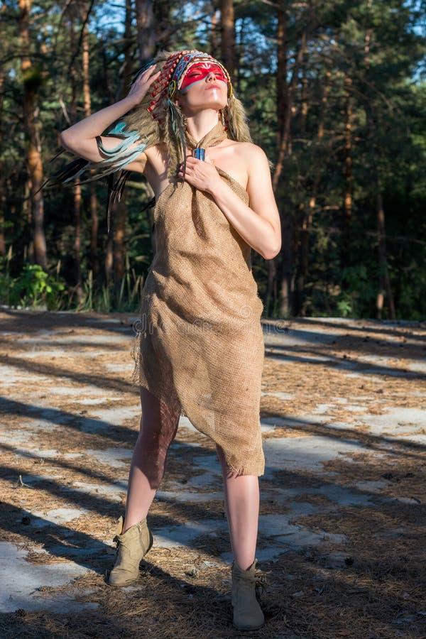 A mulher vestiu-se em um estilo indiano com os olhos fechados nas madeiras fotos de stock