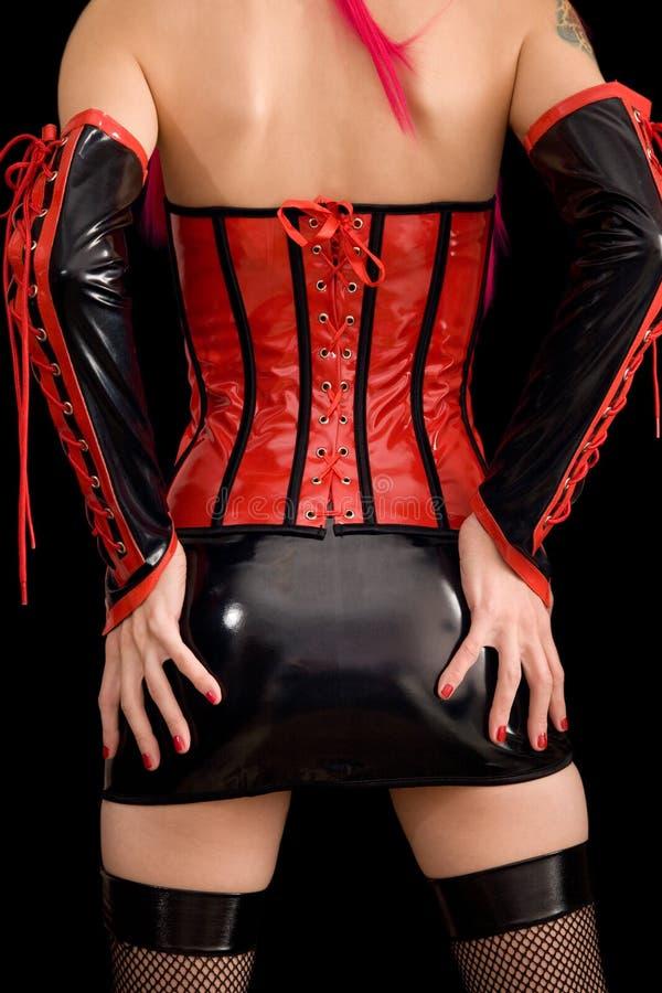 A mulher vestiu-se na roupa do dominatrix, da parte traseira foto de stock