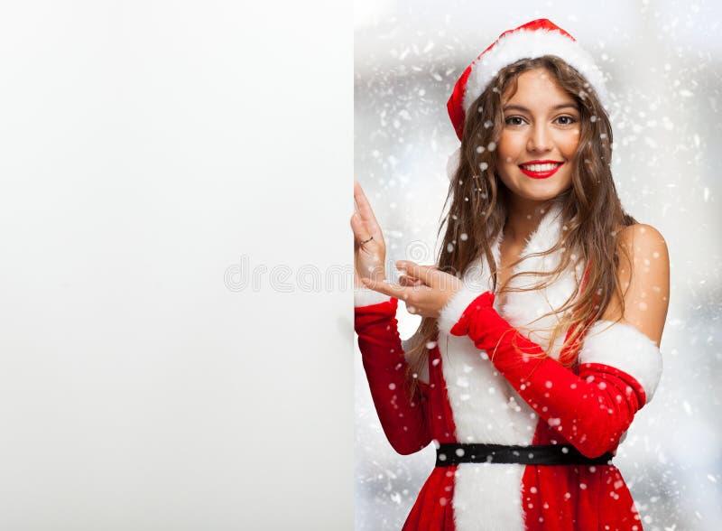 A mulher vestiu-se para o Natal que mostra uma placa vazia foto de stock royalty free