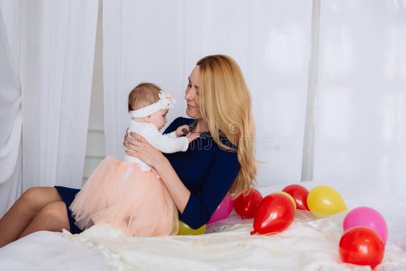 A mulher vestiu sua menina em um vestido bonito, guarda-a em seus braços e admira-a O bebê toca na colar fotografia de stock royalty free