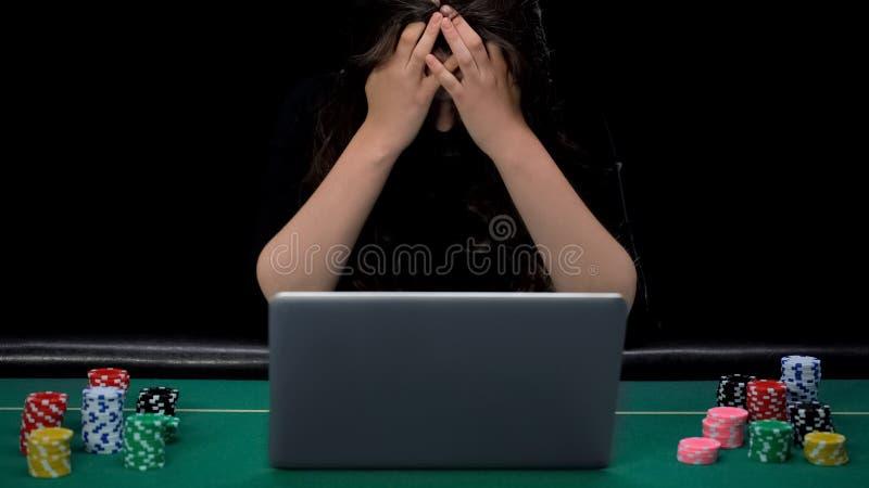 Mulher viciado de jogo que senta-se na frente do portátil, aposta perdedora do esporte do gamer triste foto de stock